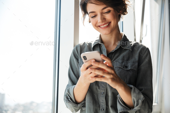 Image of beautiful young joyful woman using mobile phone and smiling - Stock Photo - Images