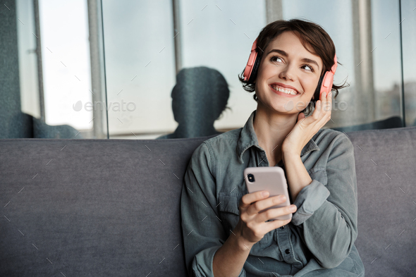 Image of nice young smiling woman using smartphone and headphones - Stock Photo - Images