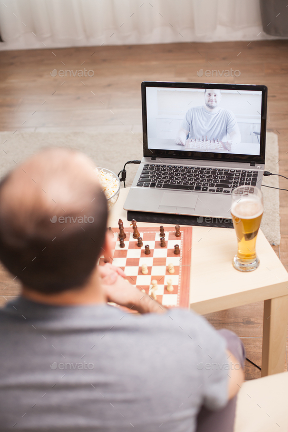 Smart men playing chess on video call - Stock Photo - Images