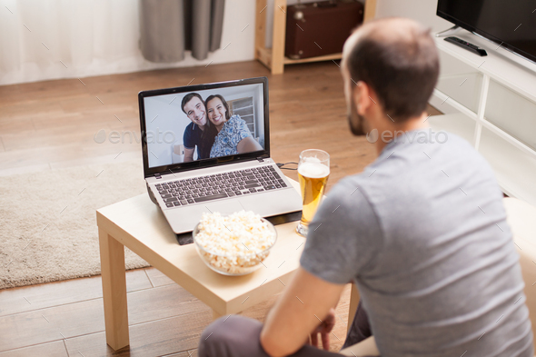 Man in a video call with his friends - Stock Photo - Images