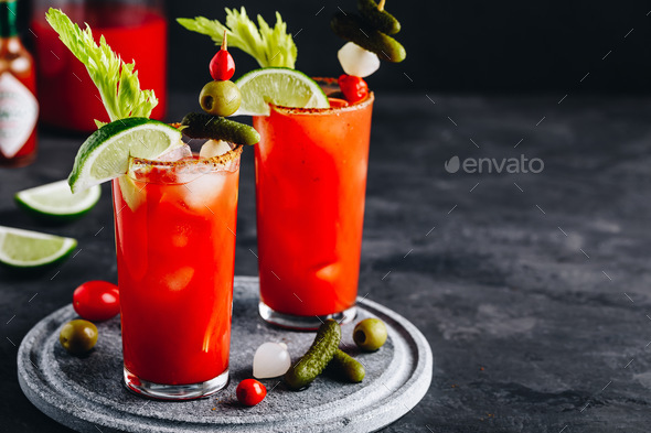 omato Bloody Mary ice cold drink with fresh celery, pickles and lime - Stock Photo - Images