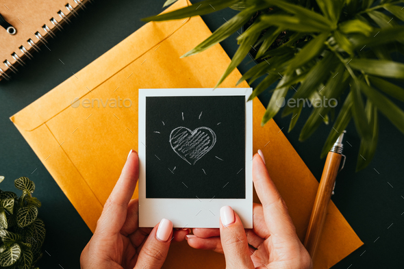 Flat lay female hand holding a polaroid picture - Stock Photo - Images