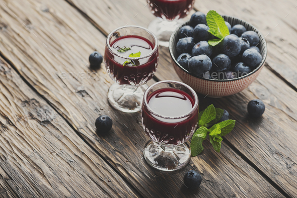 Sweet blueberry liqueur on the wooden table - Stock Photo - Images