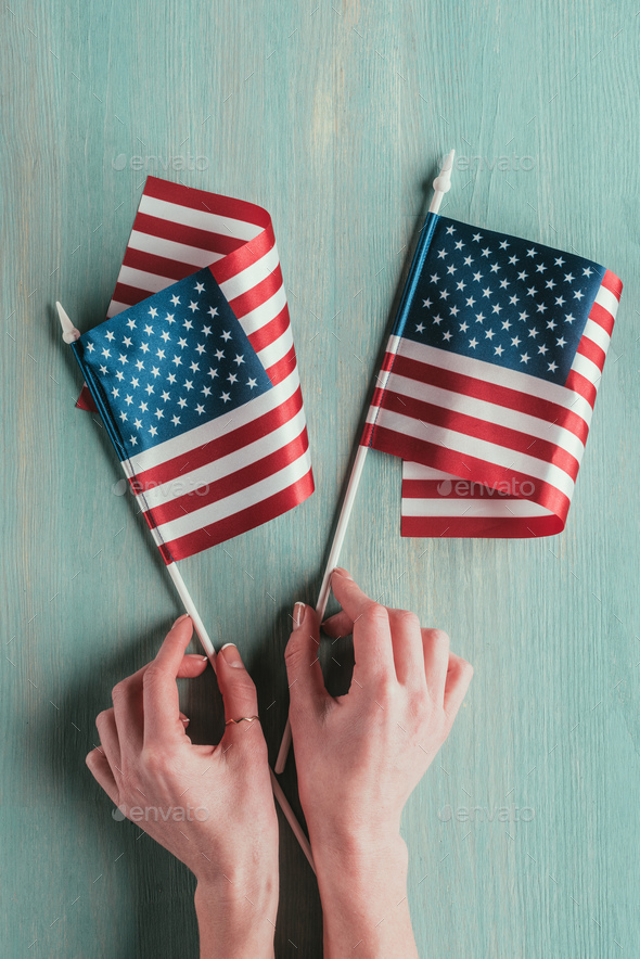 Partial View of Woman Holding American Flags in Hands on Blue Wooden Tabletop - Stock Photo - Images