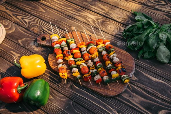Wooden Board With Vegetables And Mushrooms on Skewers Cooked Outdoors on Grill - Stock Photo - Images