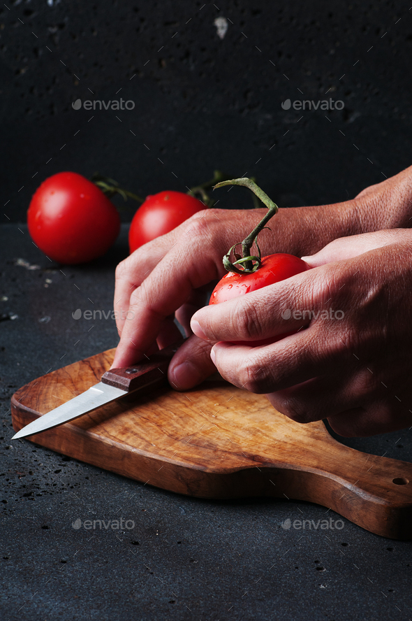 Man's hands cutting a tomato - Stock Photo - Images