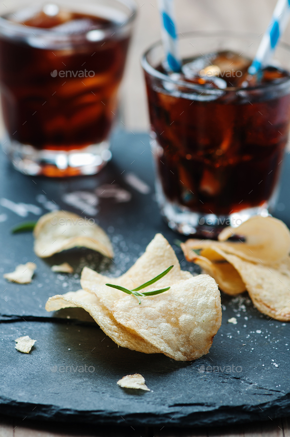 Potato chips and glass of cola on the table - Stock Photo - Images