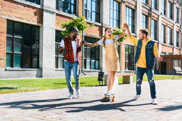 Multiethnic Men Helping Young Woman Skating on Longboard on Street - Stock Photo - Images