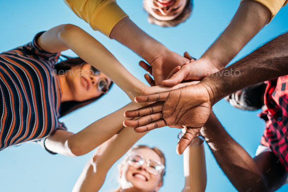 Bottom View of Multiracial Young Friends Holding Hands Together With Blue Sky on Backdrop - Stock Photo - Images