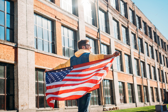 Back View of Young Man With American Flag in Hands on Street - Stock Photo - Images