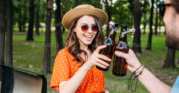 Partial View of Couple Clinking Bottles of Beer During Bbq in Park - Stock Photo - Images