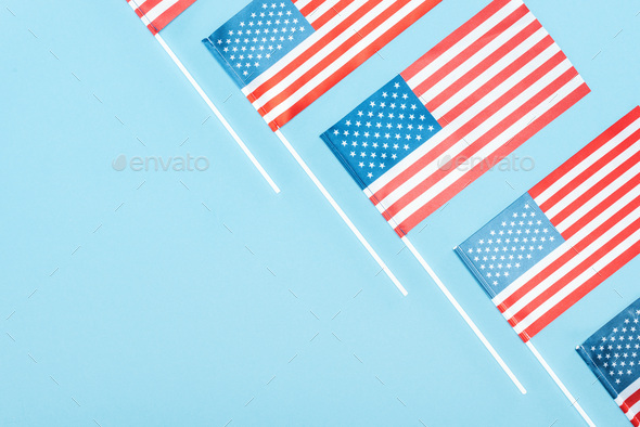 Flat Lay With American Flags on Sticks on Blue Background With Copy Space - Stock Photo - Images