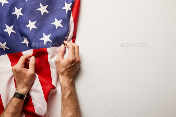 Cropped View of Man Holding American Flag on White Background With Copy Space - Stock Photo - Images