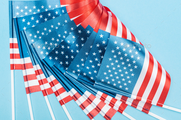 Close up View of Silk American Flags on Sticks on Blue Background - Stock Photo - Images