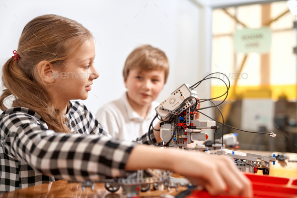 Boy and girl creating robot using building kit - Stock Photo - Images