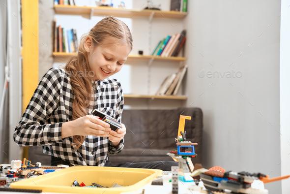 Caucasian girl using building kit - Stock Photo - Images