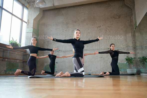 Young women practicing yoga in hall - Stock Photo - Images