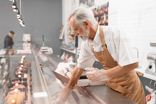 Male butcher taking raw meat out of counter - Stock Photo - Images