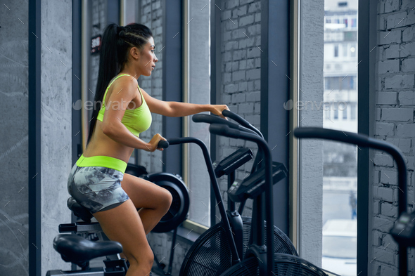 Fit woman using exercise bike - Stock Photo - Images