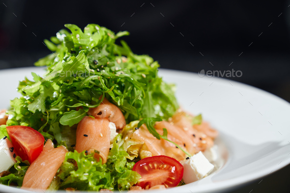 Fresh salad with salmon on plate - Stock Photo - Images
