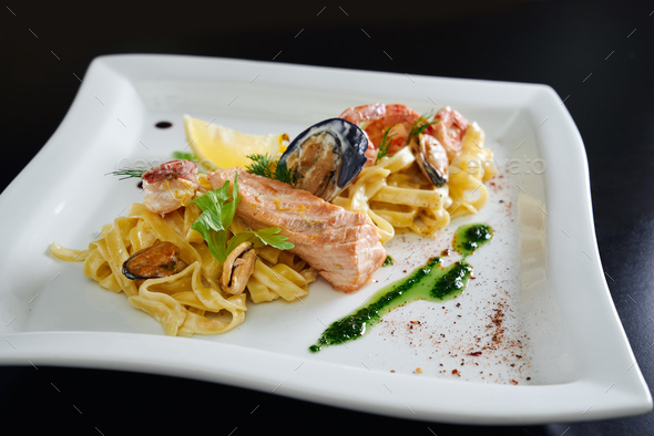 Pasta with seafood on white plate - Stock Photo - Images