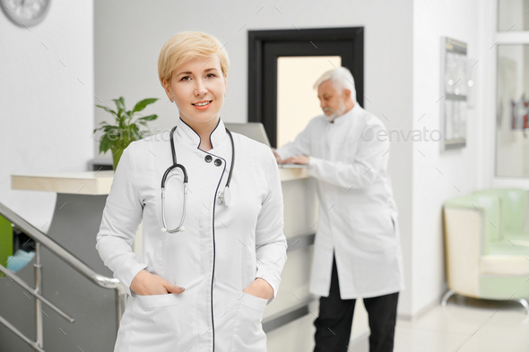 Female doctor in coat keeping hands in pockets - Stock Photo - Images