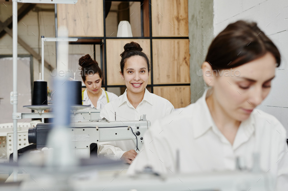 Happy young seamstress with toothy smile looking at you among her colleagues - Stock Photo - Images