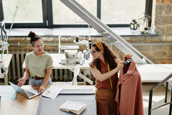Happy young designer of fashion showing her colleague new models - Stock Photo - Images