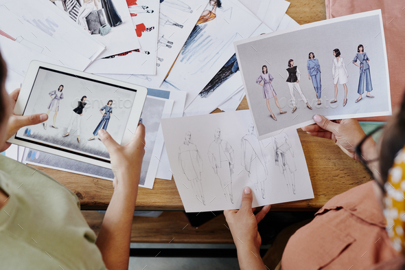 Hands of two fashion designers discussing their sketches of trendy clothes - Stock Photo - Images