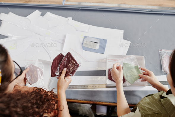 Hands of two young tailors or fashion designers choosing shoulder pads - Stock Photo - Images