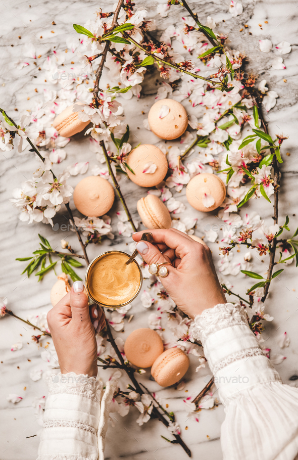 Womans hands holding fresh coffee over macaron cookies and flowers - Stock Photo - Images