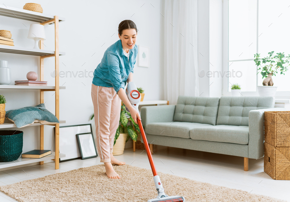 woman vacuuming the room - Stock Photo - Images
