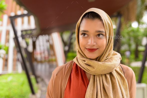 Face of young beautiful Indian Muslim woman thinking in the city with nature - Stock Photo - Images
