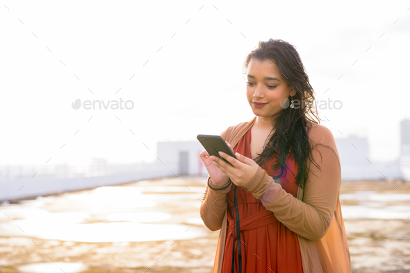 Young beautiful Indian woman using phone at rooftop of the building - Stock Photo - Images