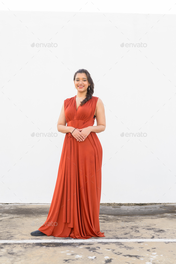 Full body shot of happy young beautiful Indian woman smiling outdoors - Stock Photo - Images