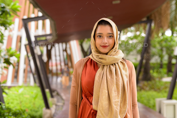 Young beautiful Indian Muslim woman in the city with nature outdoors - Stock Photo - Images