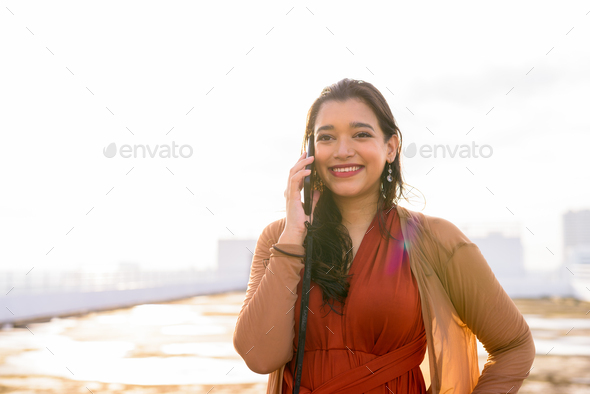 Happy young beautiful Indian woman talking on the phone at rooftop of the building - Stock Photo - Images