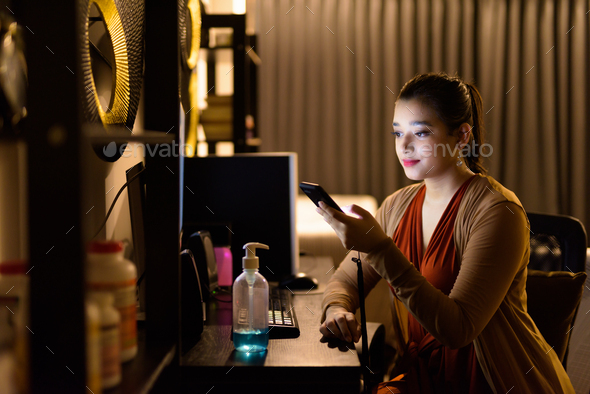 Young beautiful Indian woman using phone while working from home late at night - Stock Photo - Images