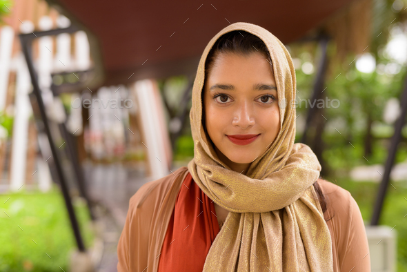Face of young beautiful Indian Muslim woman in the city with nature - Stock Photo - Images