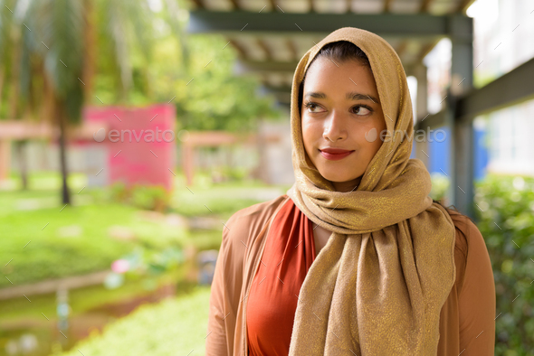 Face of young beautiful Indian Muslim woman thinking at the park - Stock Photo - Images