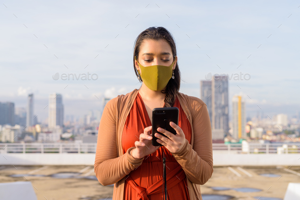 Young Indian woman with mask using phone against view of the city - Stock Photo - Images