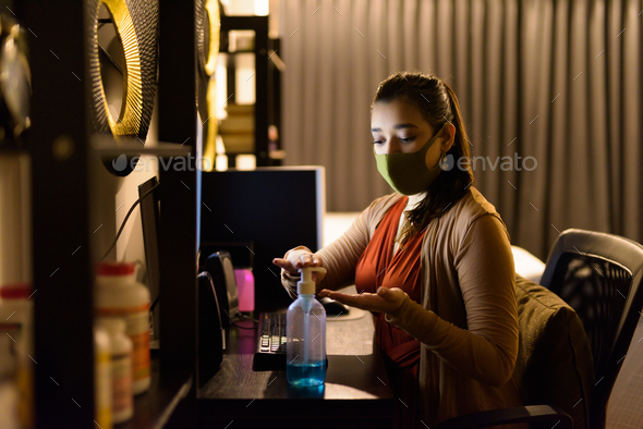 Young Indian woman with mask using hand sanitizer while working from home at night during quarantine - Stock Photo - Images