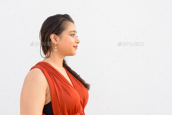 Closeup profile view of young beautiful Indian woman against white background - Stock Photo - Images