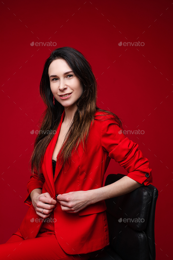 Portrait of caucasian female with long dark straight hair in red office suit, black shoes sits on - Stock Photo - Images