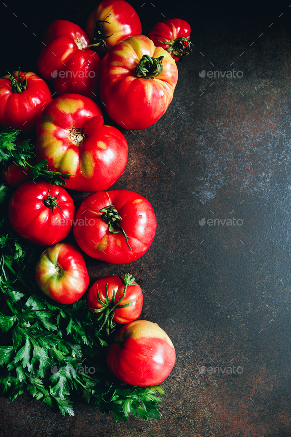 Top view of ripe tomatoes with fresh greens on a dark background. - Stock Photo - Images