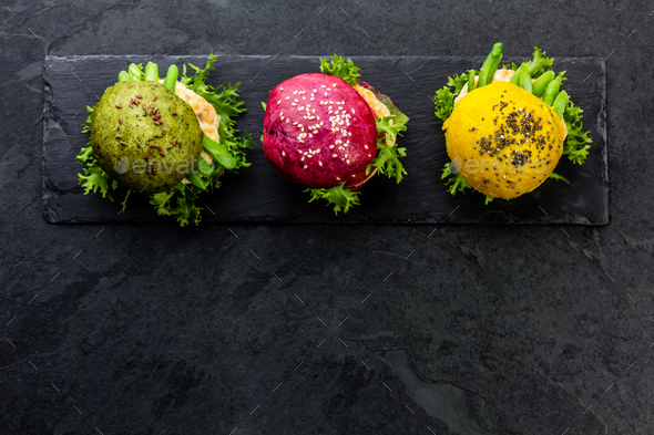 Colored green, yellow and purple burgers on slate board. Top view - Stock Photo - Images