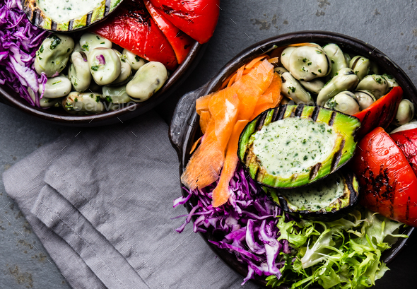 Budha bowl. Raw vegetables with beans, grilled avocado and bell pepper on slate background. Top view - Stock Photo - Images