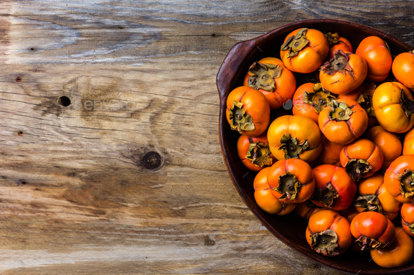 Pot of fresh fruits persimmon kaki on wooden background. Copy space - Stock Photo - Images