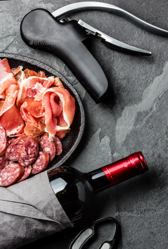 Spanish ham serrano, salami and bottle of red wine on slate - Stock Photo - Images