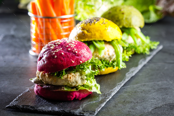 Colored green, yellow and purple burgers on slate board, slate background - Stock Photo - Images